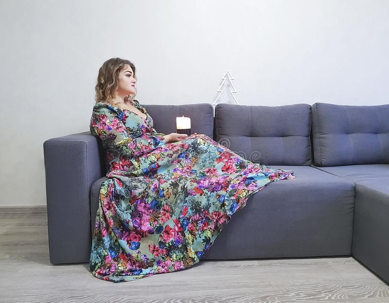 beautiful girl in dress, curly hair, candle sitting, elegant couch royalty free stock images