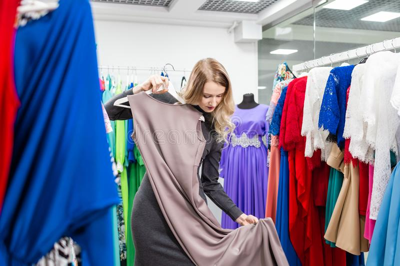 Beautiful girl with dress. Happy young woman choosing clothes in mall or clothing store. Sale, fashion, consumerism royalty free stock photography