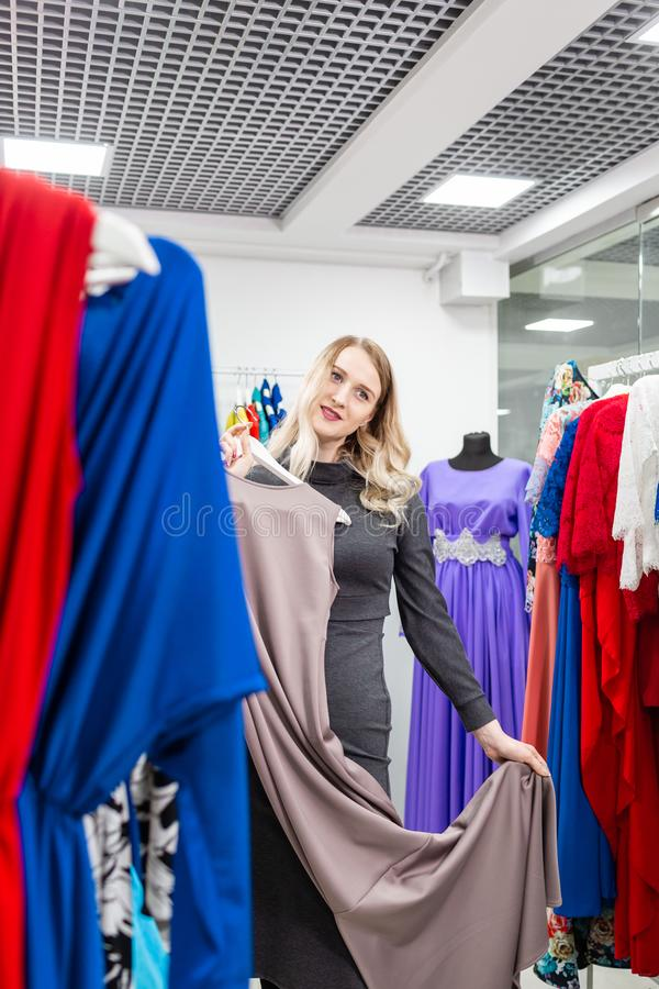 Beautiful girl with dress. Happy young woman choosing clothes in mall or clothing store. Sale, fashion, consumerism stock image