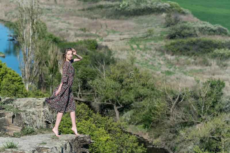 Beautiful girl in dress poses on rock in nature stock photo