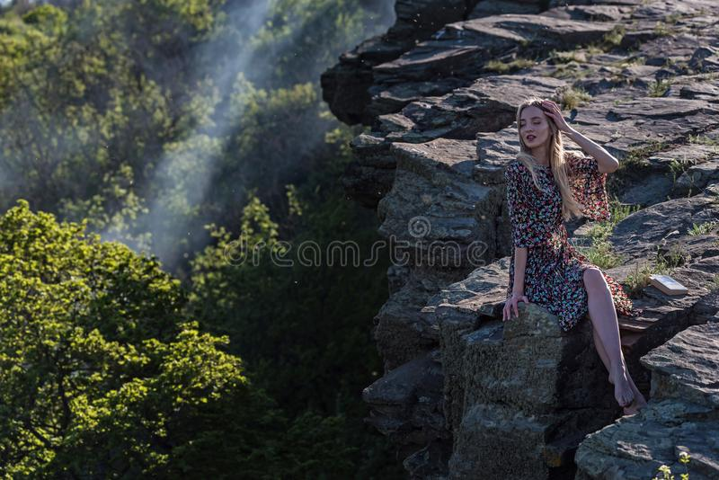 Beautiful girl in dress sits on rock in nature royalty free stock photography