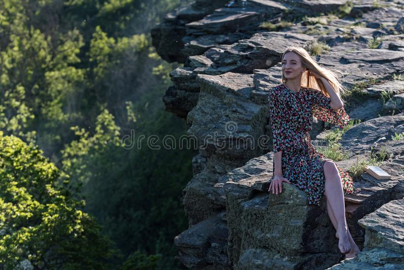 Beautiful girl in dress sits on rock in nature stock photo