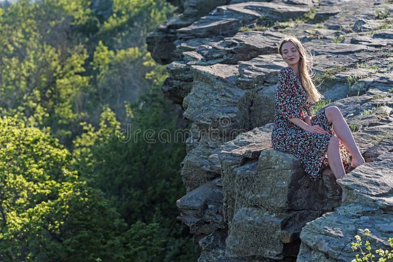 Beautiful girl in dress sits on rock in nature stock photography