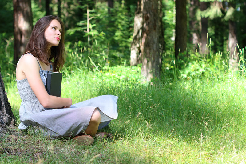 Beautiful girl in dress sitting on grass under tree with book stock photo