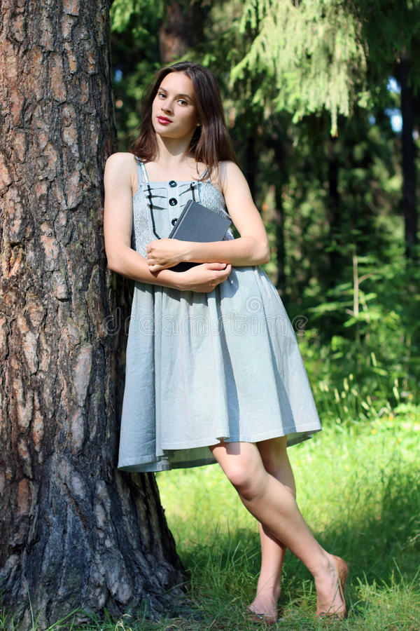 Beautiful girl in dress standing leaning against tree with book stock photos