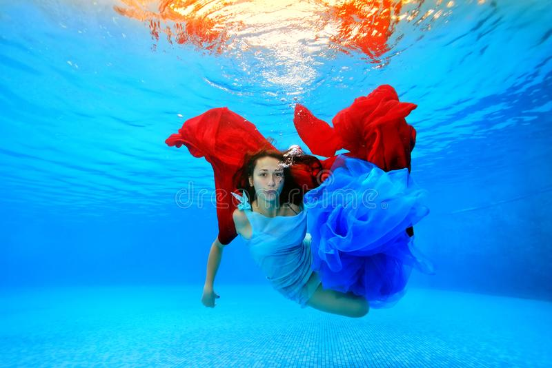 A beautiful girl in a dress swims underwater in the pool, plays with a red and blue cloth and looks at the camera. stock photos
