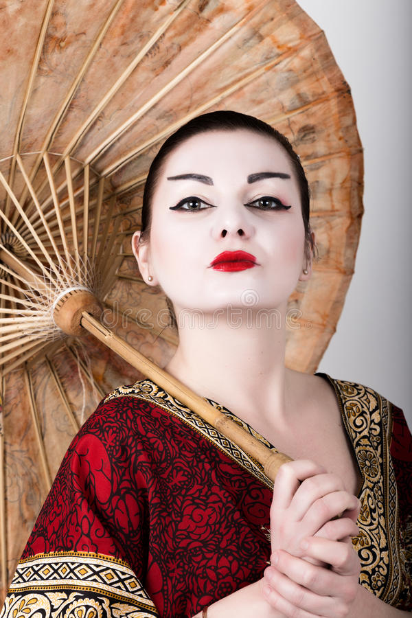 Beautiful girl dressed as a geisha girl holding a Chinese umbrella. Geisha makeup and hair dressed in a kimono. The stock photos