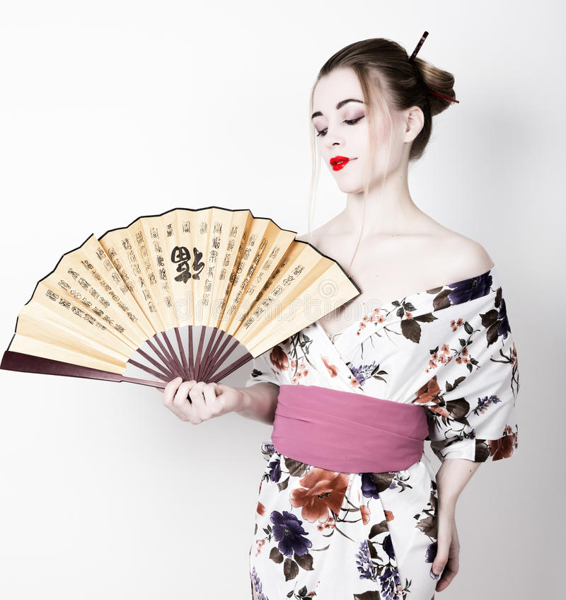 Beautiful girl dressed as a geisha, she holds a chinese fan. Geisha makeup and hair dressed in a kimono. The concept of. Traditional Japanese values royalty free stock image