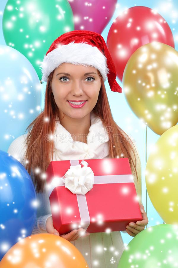 Beautiful girl dressed as Santa with. A gift box royalty free stock photo