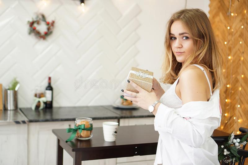 Beautiful girl dressed in a white shirt holding a gift in modern bright kitchen royalty free stock images