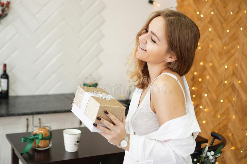 Beautiful girl dressed in a white shirt holding a gift in modern bright kitchen royalty free stock photo