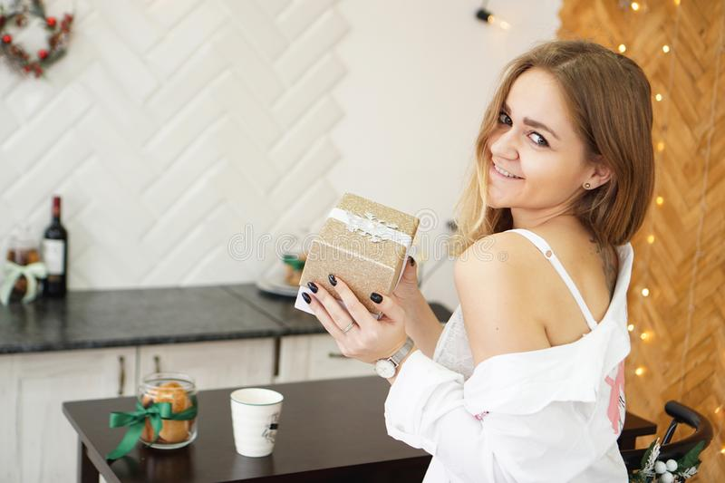Beautiful girl dressed in a white shirt holding a gift in modern bright kitchen stock image