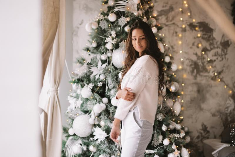 Beautiful girl dressed in white sweater and pants stands next to the New Year tree in front of the window in a cozy. Decorated room stock images