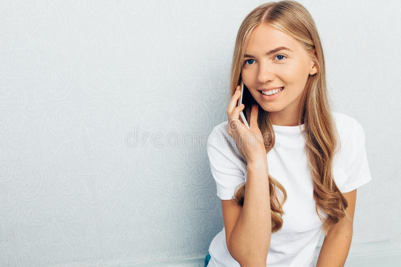 Beautiful girl dressed in a white t-shirt, talking on the phone, on a gray background royalty free stock image