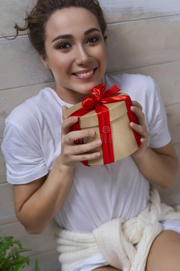 A beautiful girl dressed in a white tshirt, a sweater tied to th stock image
