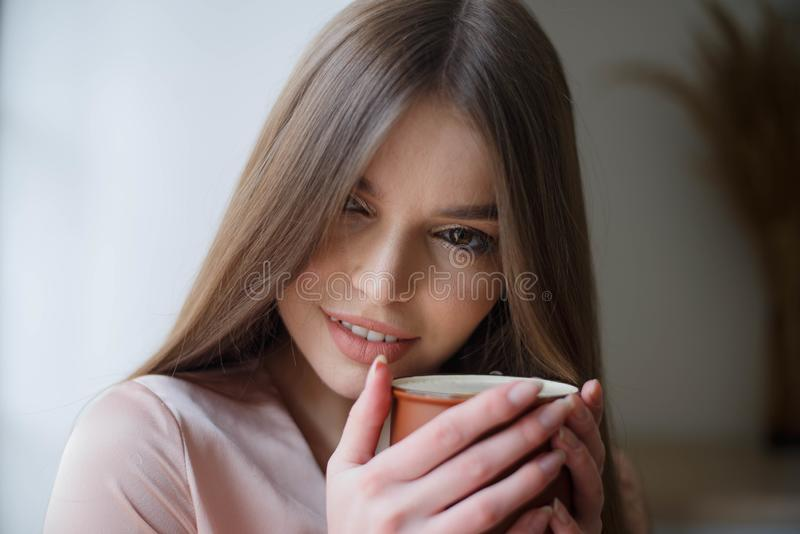 Beautiful girl is drinking coffee and smiling while sitting at the cafe stock images