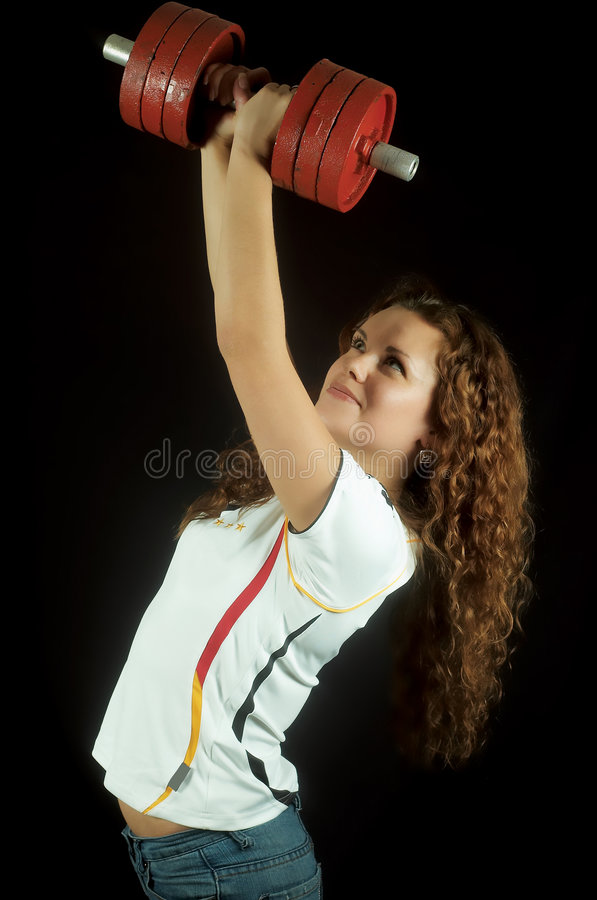 Beautiful girl with dumbbells. The beautiful young girl lifts heavy dumbbell stock image