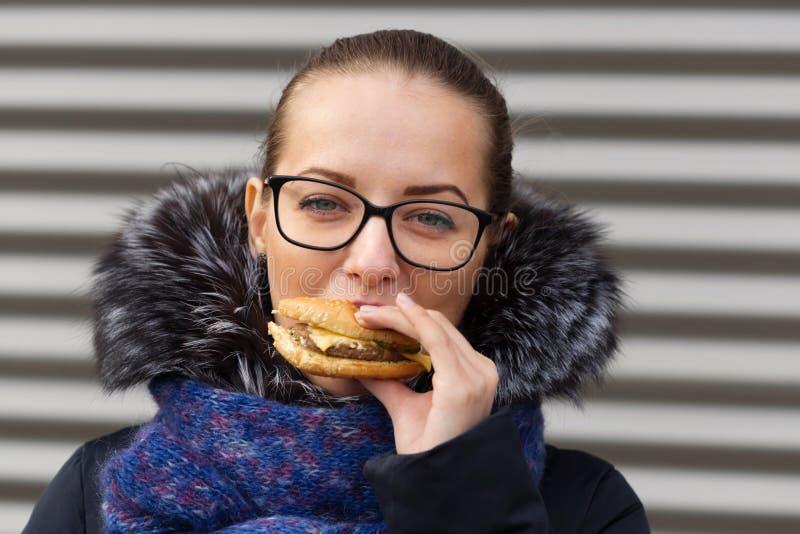 Beautiful girl eagerly eats a hamburger on the street.  stock photo