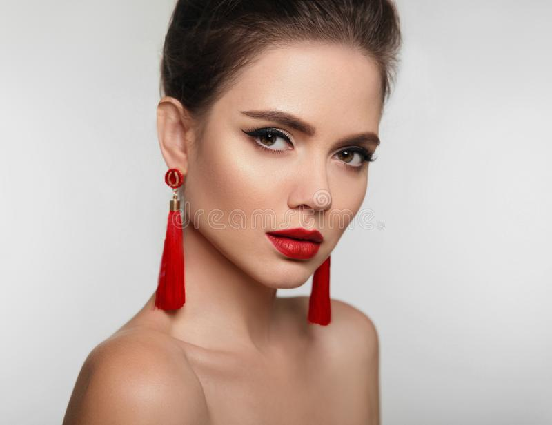 Beautiful girl with earrings jewelry. Beauty face of young brunette woman with a bright make-up and red lips isolated on studio b royalty free stock image