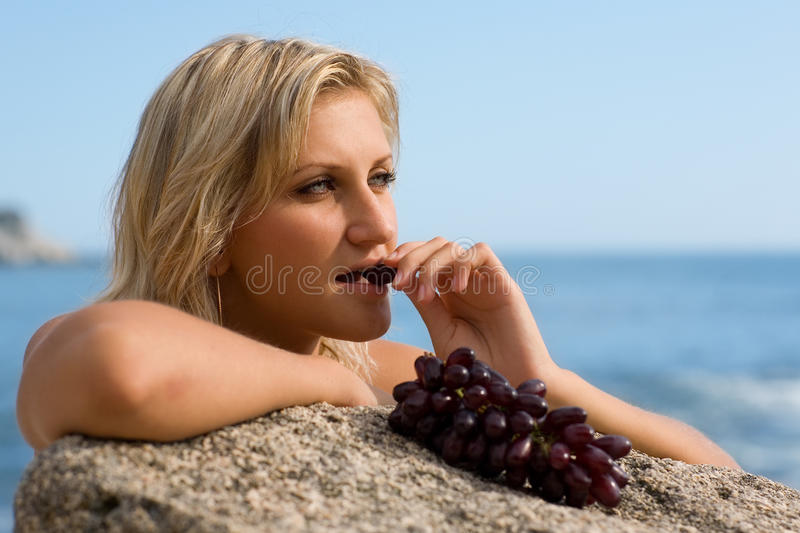 Beautiful girl eating grapes. At the beach by the sea stock image