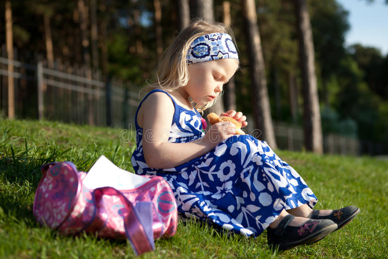 Beautiful girl eating muffin is on green grass. royalty free stock photo