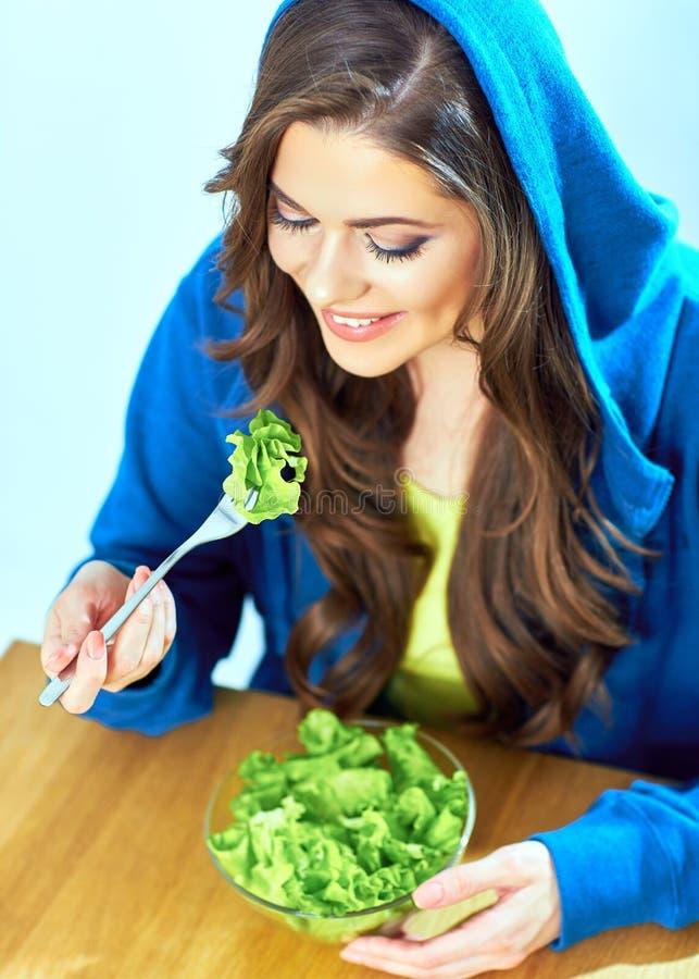 Beautiful girl eating salad. female portrait. Vegetarian diet royalty free stock image