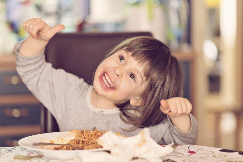 Beautiful girl eating spaghetti making faces stock photos