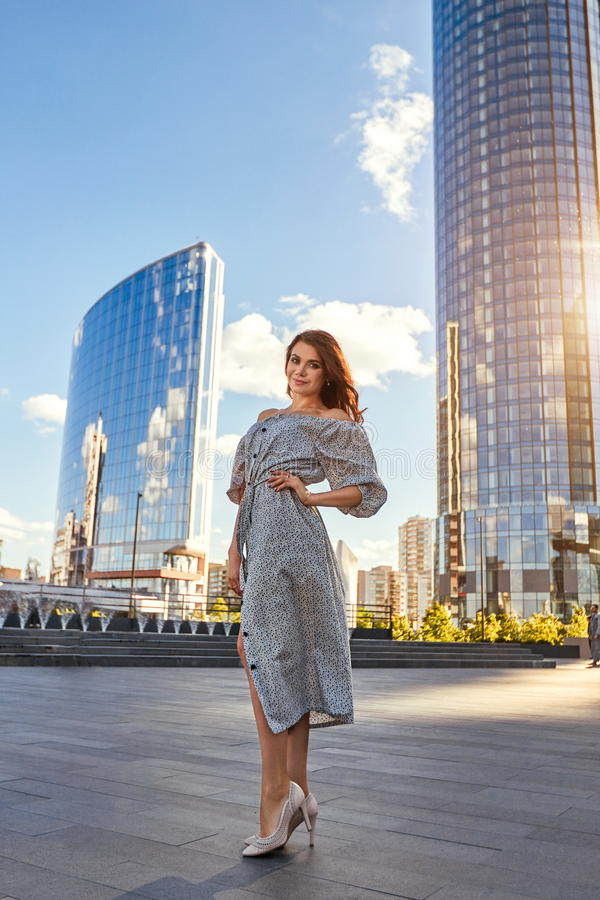 Beautiful girl in elegant dress and charming smile posing for the photographer in the city of Yekaterinburg. Business girl walks after work royalty free stock images