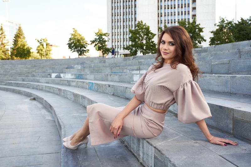 Beautiful girl in elegant dress and charming smile posing for the photographer in the city of Yekaterinburg. Business girl walks after work royalty free stock photo