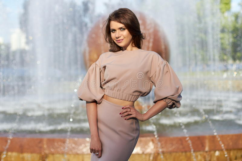 Beautiful girl in elegant dress and charming smile posing for the photographer in the city of Yekaterinburg. Business girl walks after work royalty free stock image