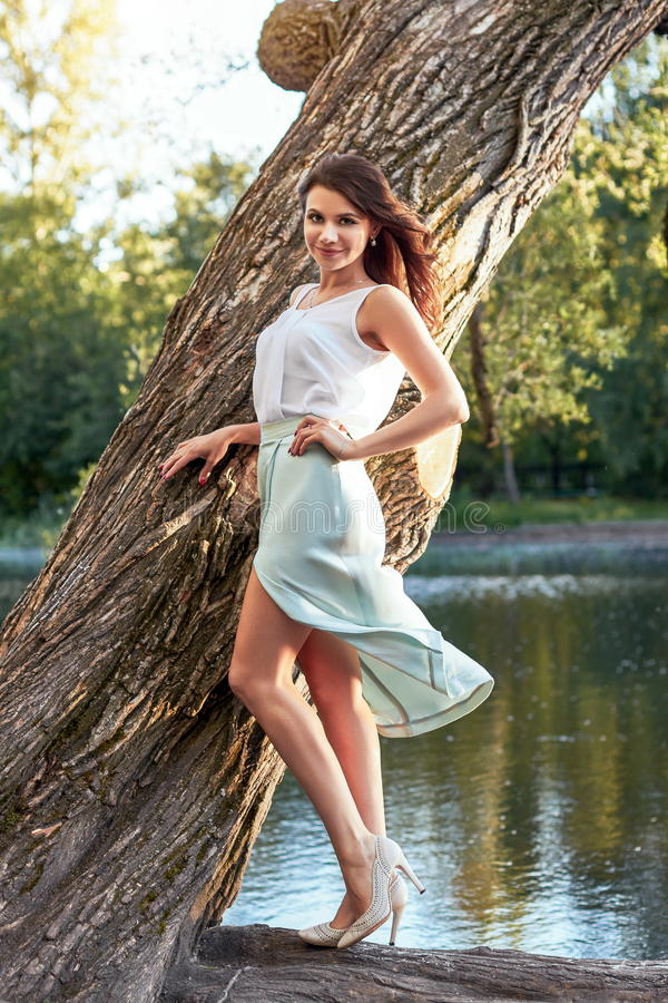 Beautiful girl in elegant dress and charming smile posing for the photographer in the park of Yekaterinburg. Beautiful girl in elegant dress and charming smile stock photography