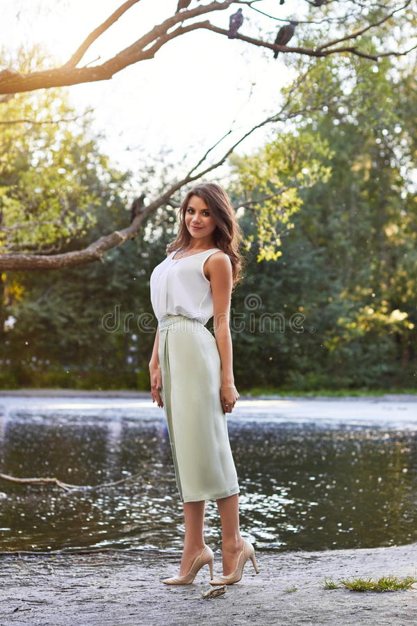 Beautiful girl in elegant dress and charming smile posing for the photographer in the park of Yekaterinburg. Beautiful girl in elegant dress and charming smile stock images