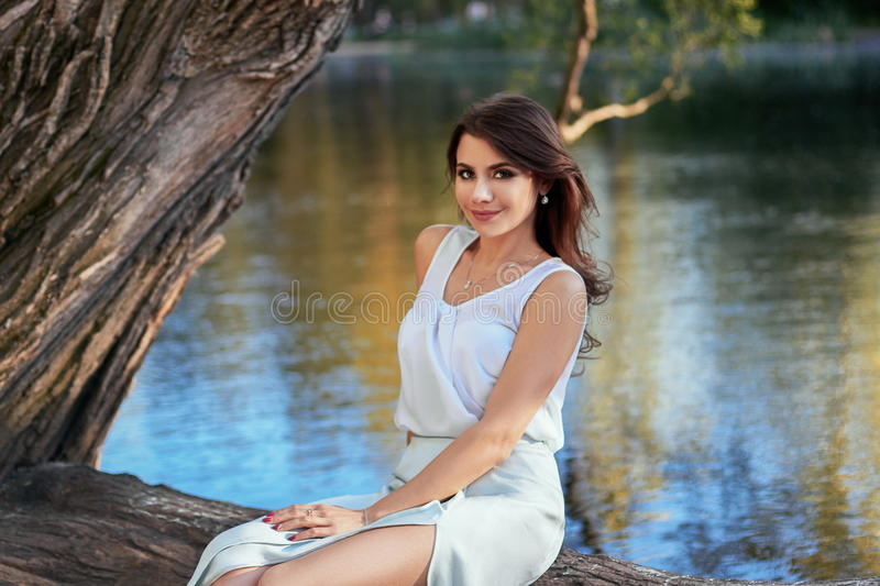 Beautiful girl in elegant dress and charming smile posing for the photographer in the park of Yekaterinburg. Beautiful girl in elegant dress and charming smile royalty free stock photo