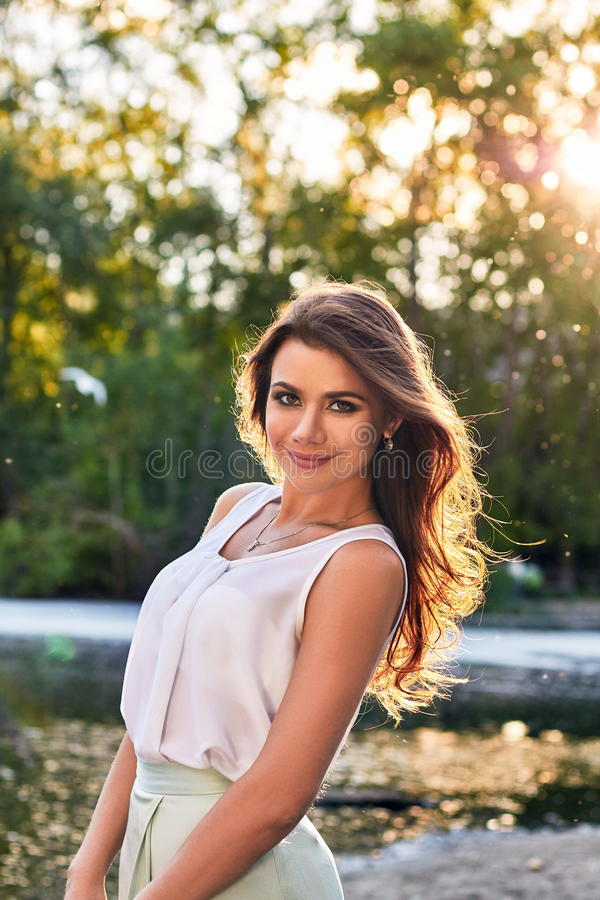 Beautiful girl in elegant dress and charming smile posing for the photographer in the park of Yekaterinburg. Beautiful girl in elegant dress and charming smile royalty free stock image