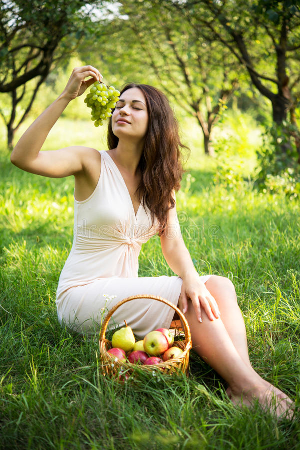 A beautiful girl enjoys the aroma of grapes royalty free stock images