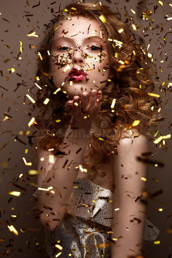 Beautiful girl in an evening dress and gold curls. Model in New Year`s image with glitter and tinsel. Holiday picture. Christmas atmosphere. Beauty face royalty free stock photo