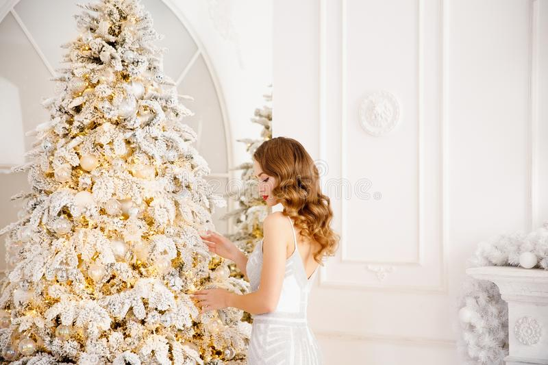 Beautiful girl in evening dress with make-up and hair decorates Christmas tree white balls, back view with sun light.  stock photos