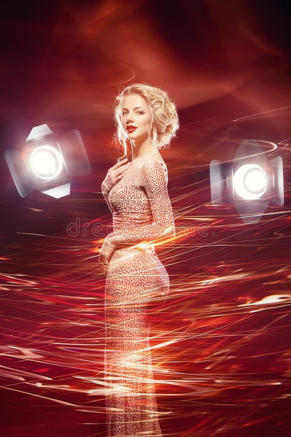 Beautiful girl in evening dress surrounded by light. Beautiful happy young woman with stunning figure and bright makeup wearing evening dress surrounded by light stock photo