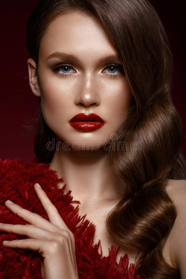 A beautiful girl with evening make-up, a Hollywood wave and red lips. Beauty face. Photo taken in the studio stock photo