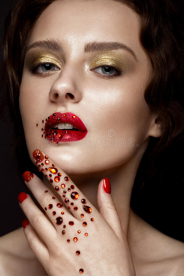Beautiful girl with evening make-up, red lips in rhinestones and design manicure nails. beauty face. stock photo
