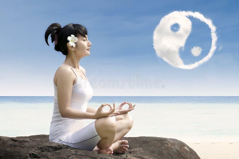 Beautiful girl exercise yoga at beach under ying yang cloud stock images