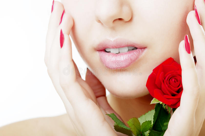 Beautiful girl face close up with a rose in hand. The image of a beautiful girl face close up with a rose in hand royalty free stock photo