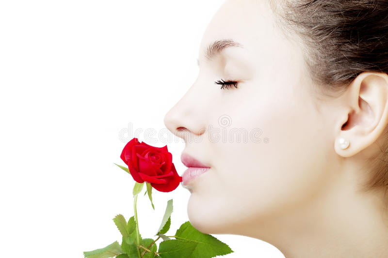 Beautiful girl face close up with a rose in hand. The image of a beautiful girl face close up with a rose in hand stock image