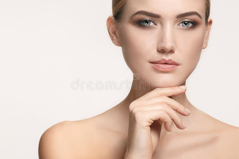 Beautiful Girl face. Perfect skin. The beautiful female face. The perfect and clean skin of face on white stock photo