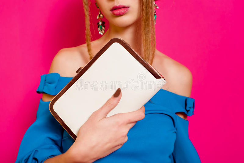 Beautiful girl in fashion dress with clutch royalty free stock photo
