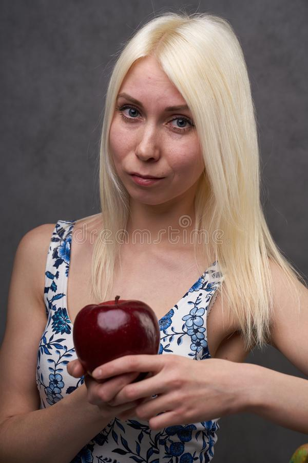 Beautiful girl in a fashionable dress with apple. Portrait composition stock photos
