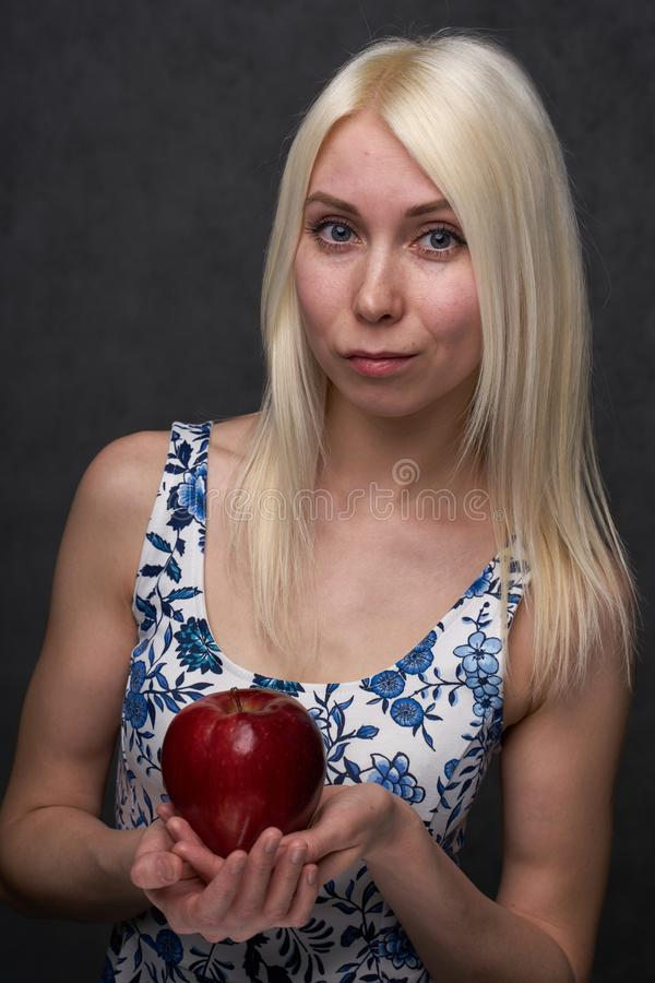 Beautiful girl in a fashionable dress with apple. Portrait composition royalty free stock photography