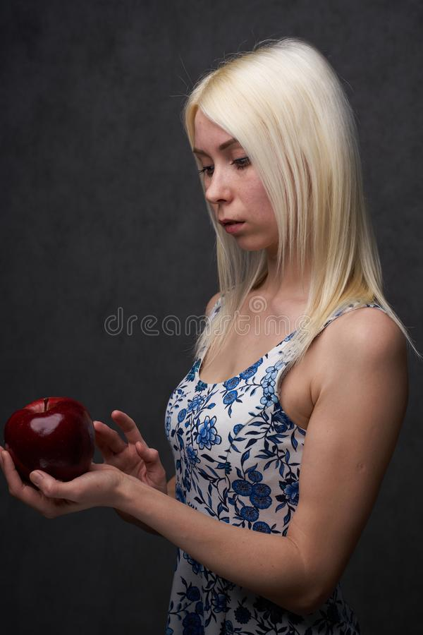 Beautiful girl in a fashionable dress with apple. Portrait composition stock images
