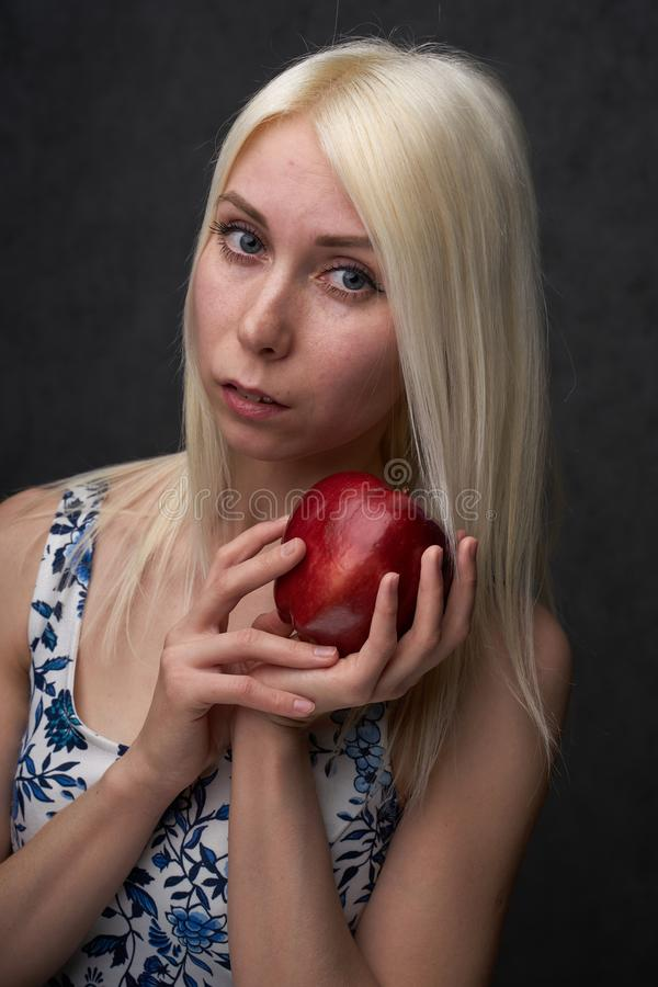 Beautiful girl in a fashionable dress with apple royalty free stock photo