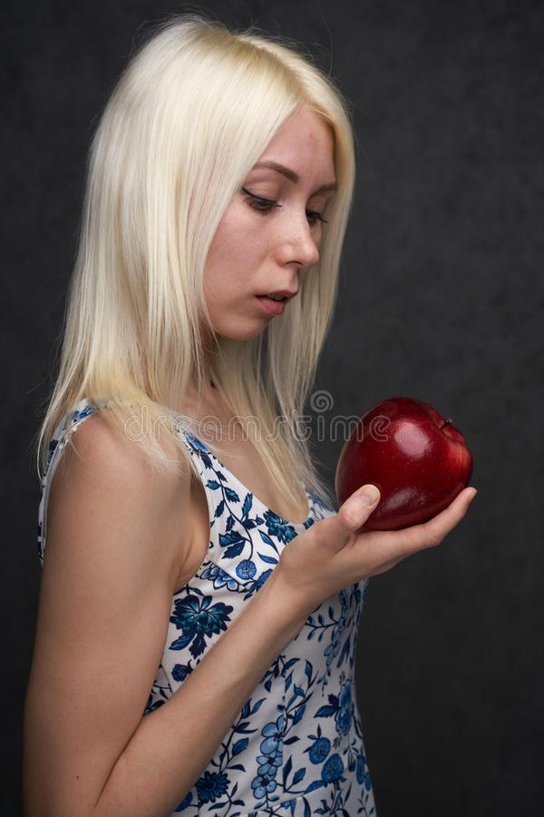 Beautiful girl in a fashionable dress with apple. Portrait composition royalty free stock photo